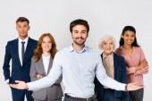 Veselý podnikatel ukazuje rukama poblíž multietnických kolegů izolovaných na šedé
