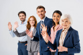 Smiling businessman waving hand at camera near multicultural colleagues on blurred foreground isolated on grey