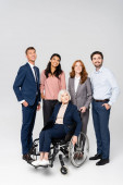 Smiling multiethnic businesspeople looking away near senior woman in wheelchair on grey background