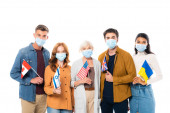 Photo Multicultural people in medical masks holding flags and looking at camera isolated on white