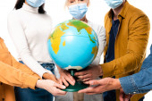 Cropped view of multiethnic people in medical masks holding globe isolated on white