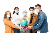 Multicultural people in medical masks looking at camera while holding globe isolated on white