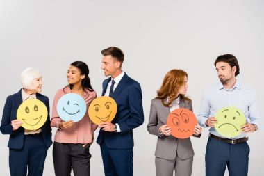 Smiling and sad multiethnic businesspeople holding cards with emotions while talking isolated on grey stock vector