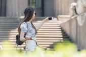 boční pohled na mladé atraktivní ženy v sluneční brýle s selfie na smartphone na ulici