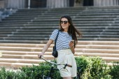Fotografie portrait of young smiling woman with smartphone and retro bicycle on street