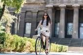 Junge lächelnde Frau mit Sonnenbrille Retro-Fahrrad auf der Straße