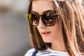 Photo portrait of of beautiful young woman in sunglasses on street