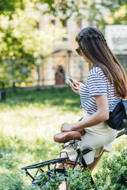 side view of young attractive woman using smartphone while leaning on bicycle in park