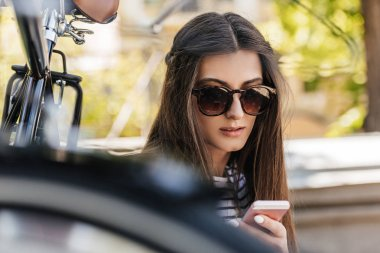 portrait of young woman using smartphone while sitting near retro bicycle on street