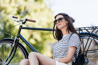 stylish young woman in sunglasses with retro bicycle resting on street
