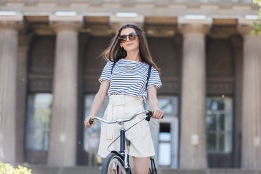 portrait of stylish young woman in sunglasses with retro bicycle standing on street