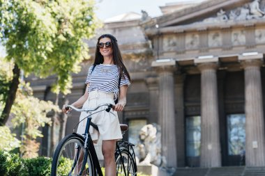 young smiling woman in sunglasses with retro bicycle on street