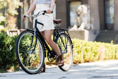 Cropped shot of woman with retro bicycle on street stock vector