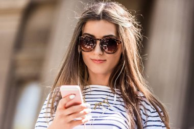 portrait of young attractive woman in sunglasses using smartphone on street