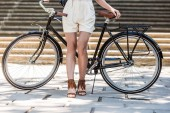 cropped shot of woman with retro bicycle on street