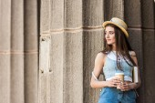 Fotografie portrait of young pensive woman with book and coffee to go on street