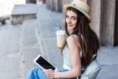 boční pohled na mladá usmívající se žena s tabletem a kávu jít sedět na schodech