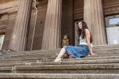 Fotografia giovane donna alla moda in occhiali e gonna di jeans che riposa sui punti sulla strada