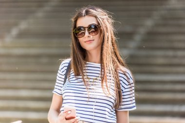 portrait of young smiling woman in sunglasses with smartphone on street