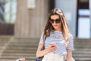 portrait of young attractive woman in earphones using smartphone on street