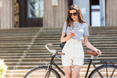 portrait of young attractive woman in earphones using smartphone while leaning on retro bicycle on street