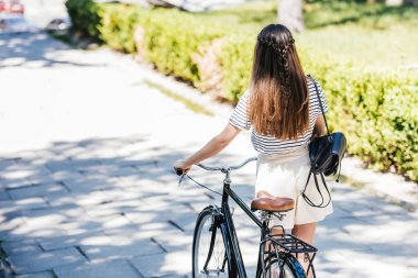 back view of woman with retro bicycle walking on street
