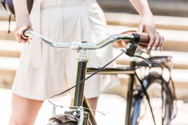 cropped shot of woman holding handlebar of retro bicycle on street