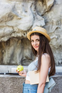 side view of young smiling woman in hat with fresh apple on street
