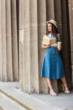 pretty pensive woman with opened book and coffee to go on street