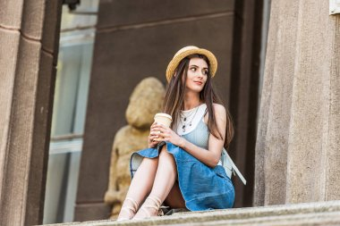 low angle view of young woman with coffee to go sitting on steps on street