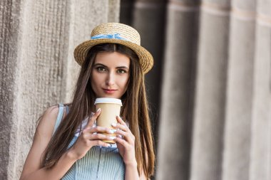 portrait of young pretty woman in straw hat with coffee to go on street