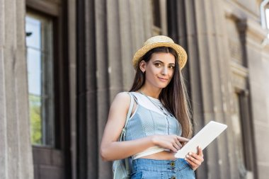 portrait of young pretty woman with digital tablet on street