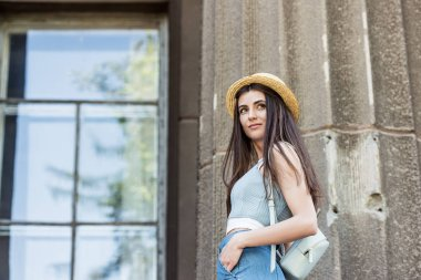 side view of young beautiful woman in straw hat on street
