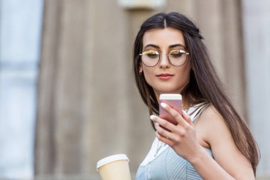 portrait of young woman in eyeglasses with coffee to go using smartphone on street