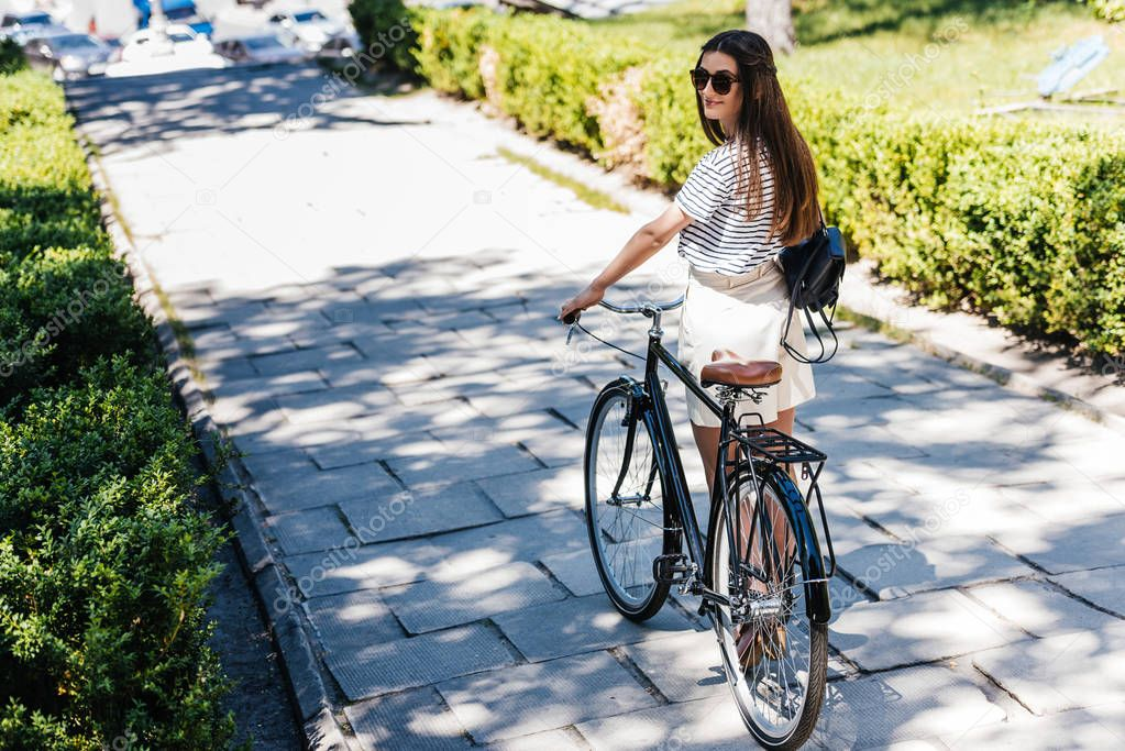back view of young woman in sunglasses with retro bicycle on street