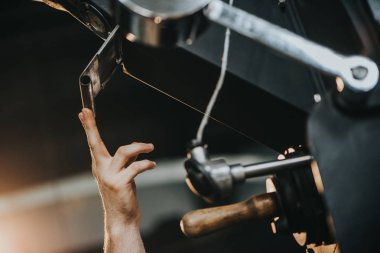 Male hand sets up machine for professional coffee production