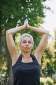 woman practicing yoga with hands in namaste gesture  in park