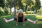 Fotografie sportive woman practicing yoga and doing positing on hands in park