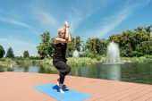 athletic woman practicing yoga and standing on one leg on yoga mat near river in park