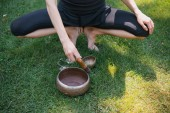 cropped image of woman squatting and making sound with tibetan singing bowls