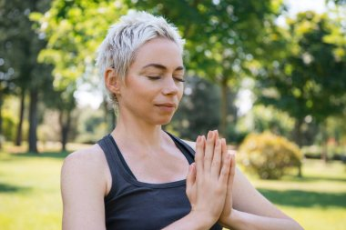 woman practicing yoga with closed eyes and making namaste gesture with hands in park