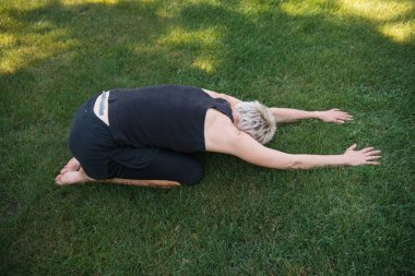 high angle view of woman practicing yoga in Extended Child pose (Utthita Balasana) on grass in park
