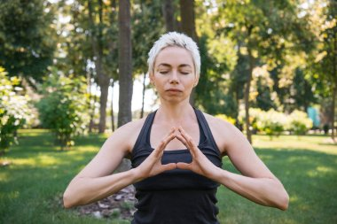 woman meditating with closed eyes in park