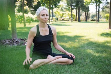 woman practicing yoga in lotus pose and looking at camera on grass in park