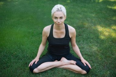 woman practicing yoga in lotus pose on green grass in park