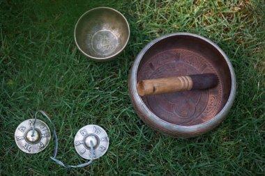tibetan singing bowls on green grass in park