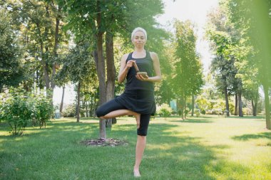 attractive woman practicing yoga in tree pose and making sound with tibetan singing bowl in park