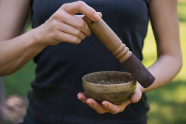 cropped image of woman making sound with tibetan singing bowl