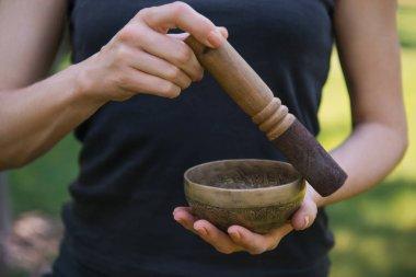 cropped image of woman making sound with tibetan singing bowl