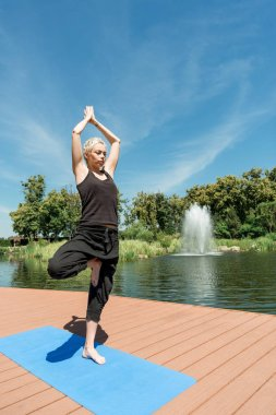 woman practicing yoga in Tree pose (Vrksasana) on yoga mat near river in park